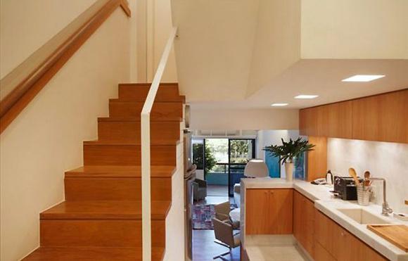 Madeira de peroba na cozinha e na escada, para reforçar a integração dos espaços