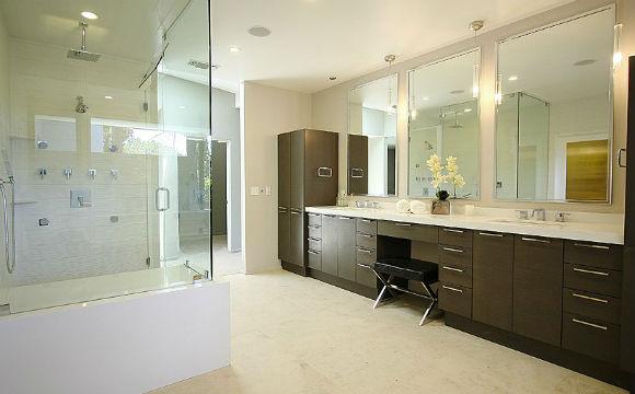 Uma pessoa que gosta de muita festa, como Miley Cyrus, precisa de um bom lugar para relaxar. O banheiro da estrela pop tem grandes espelhos, armário com muitas gavetas e uma ducha central (Foto: Reprodução/Zillow)