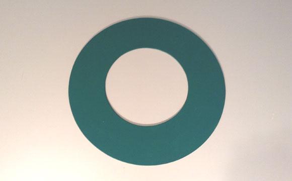 Recorte dois papelões com 30 centímetros de diâmetro (use o transferidor para fazer o desenho), sendo o círculo interno com 20 cm. Após o recorte, pinte os papelões com tinta verde acrílica e cole uma na outra