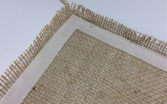 No verso do tecido, inicie a aplicação da fita dupla-face, deixando uma margem de 2 cm para dobra em todos os lados