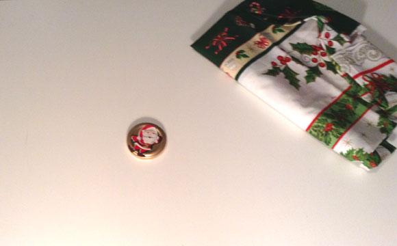 Pegue o tecido em algodão natalino, recorte os enfeites, como o Papai Noel, árvore e a bota e cole na tampa com cola bastão